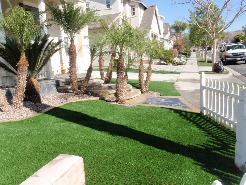 Artificial grass on both sides of a polished stone walkway with rounded steps leading to a porch