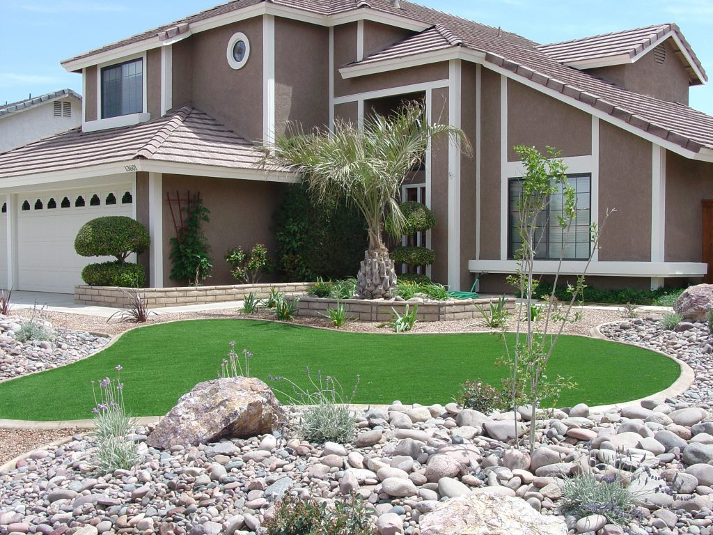 Artificial turf in front yard bordered by concrete ring and gravel with larger rocks
