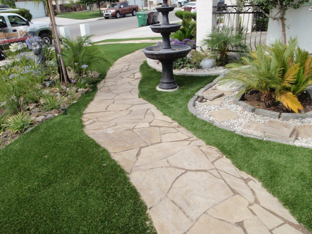Artificial turf bordering winding rock path