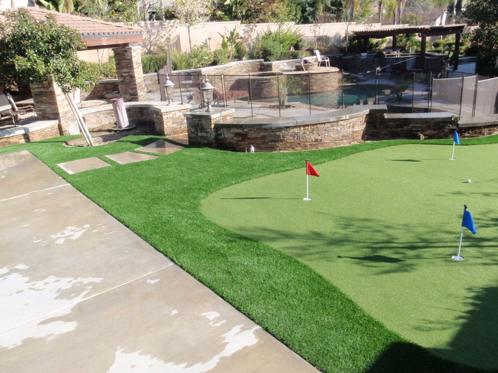 Large backyard with a swimming pool, gazebo, and a a putting green which uses artificial grass