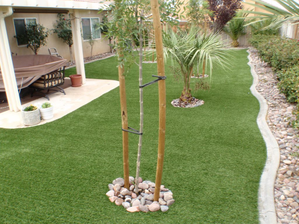 Long rectangular backyard with winding edge filled with artificial grass