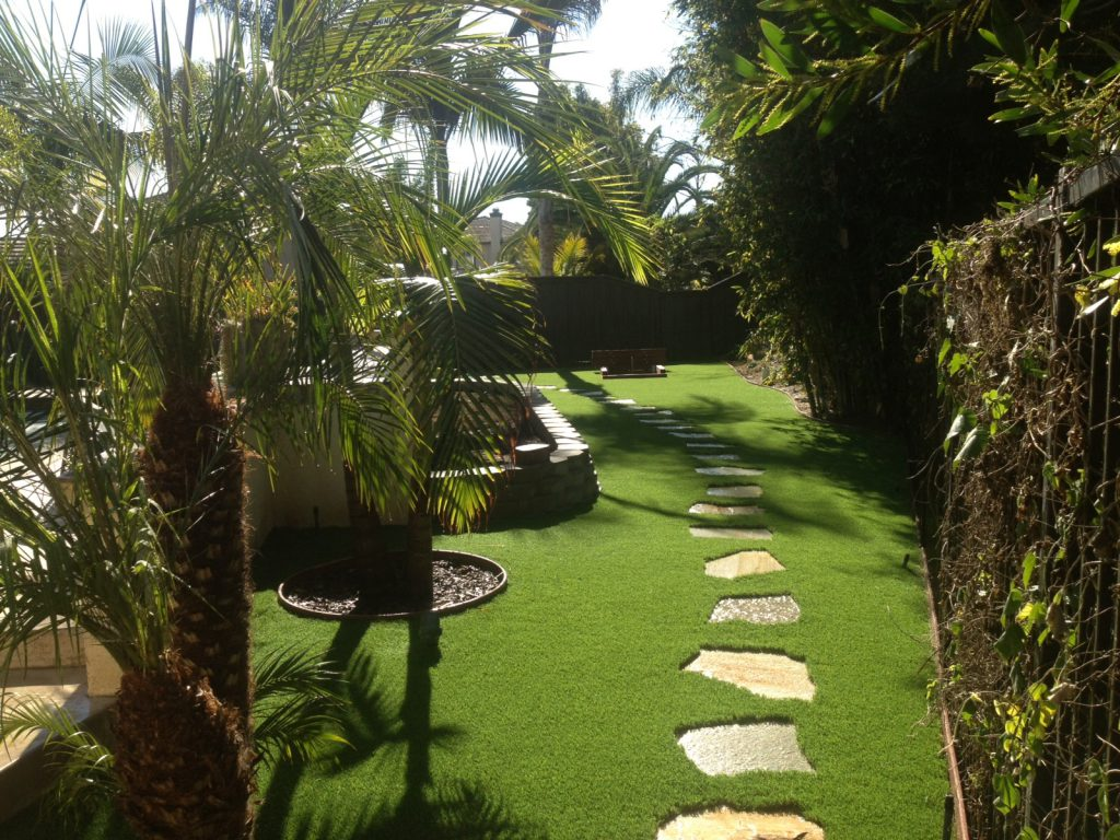 Long pathway of irregular stepping stones cutting into yard made of artificial grass