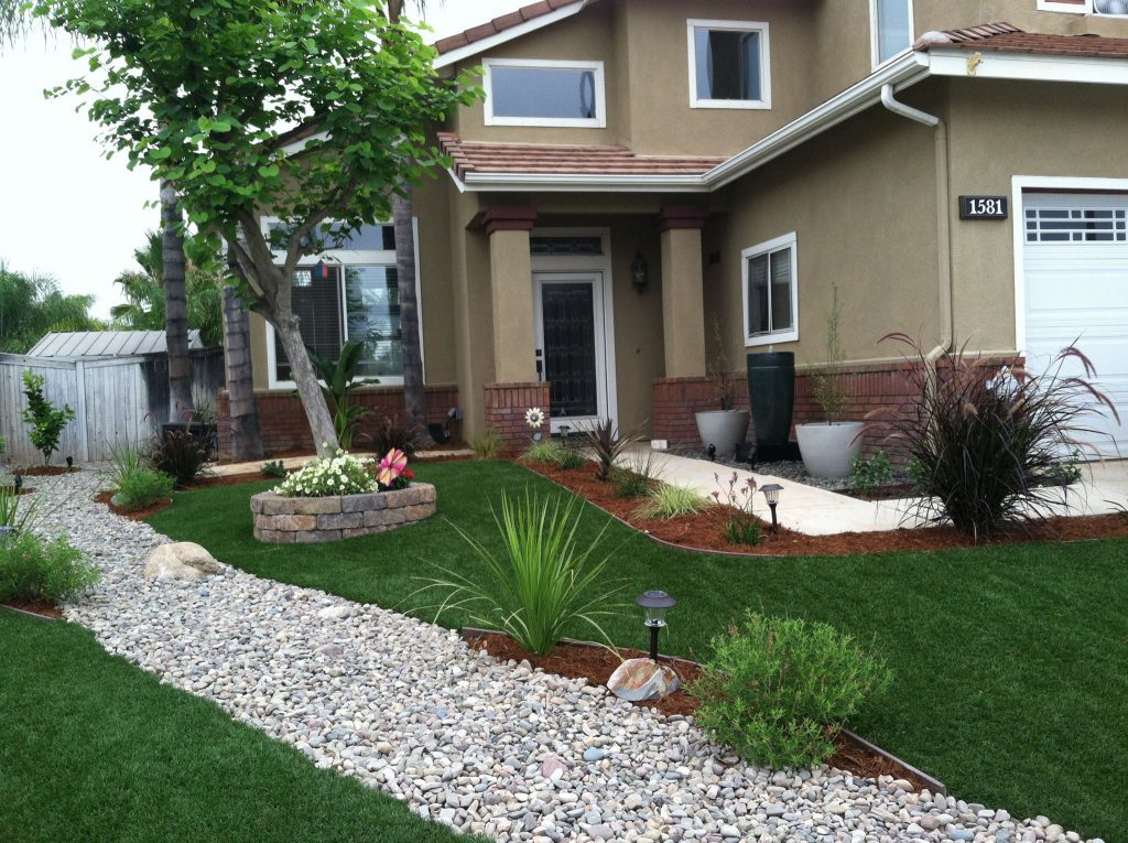 Complex front yard using artificial grass to fill the ground between a row of plants and a gravel path
