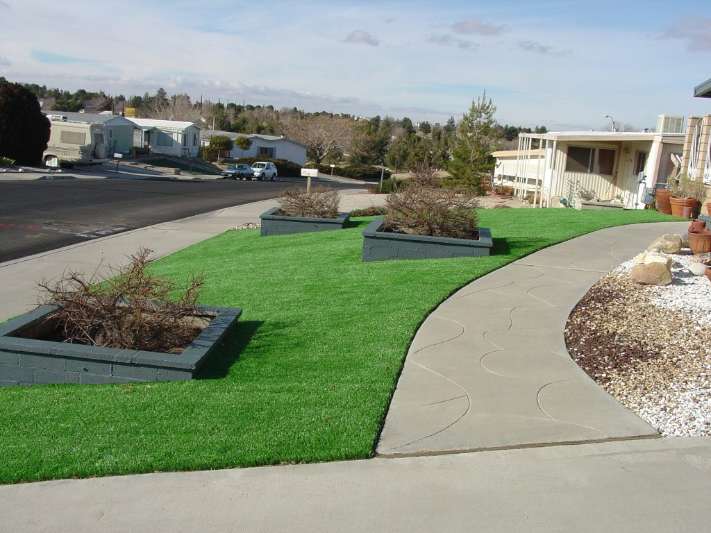 Area of artificial grass curving along driveway walk path and contains multiple enclosed areas with shrubs
