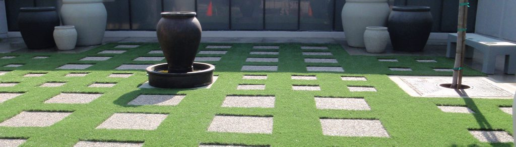 Courtyard with artificial grass and stepping stones forming a grid pattern