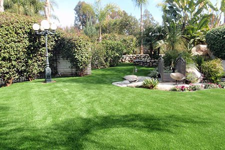 Large winding backyard with artificial grass