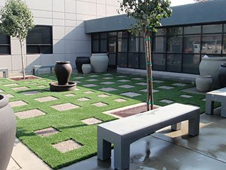 Office courtyard with stepping stones and artificial grass forming a grid pattern